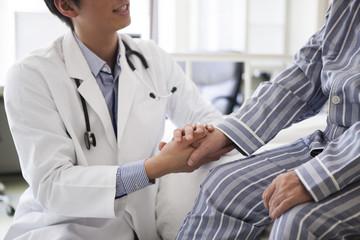 医療用ベッドで医師の診断を受ける高齢者の男性。