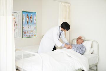 若い医師と、病室のベッドで横になっている高齢者の患者。