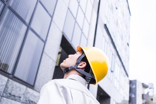 ビルを見上げる作業着の男性