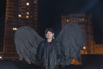 Handsome boy with black wings in night city