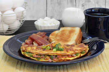 Western Omelet breakfast with toast and bacon.  Selective focus on omelet.
