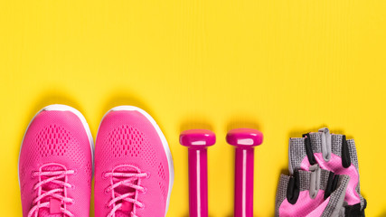 pink sneakers, gloves and dumbbells lie in a row on a yellow background, a place for an inscription