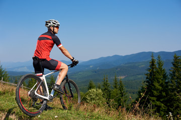 Young athletic professional tourist stopped on top of hill to enjoy beautiful view of distant Carpathian mountains on blue summer sky background. Active lifestyle and extreme sport concept.