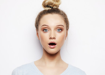 Indoor shot of stupefied shocked blonde woman keeps mouth widely opened, looks at camera, wears casual clothes, isolated over white background.