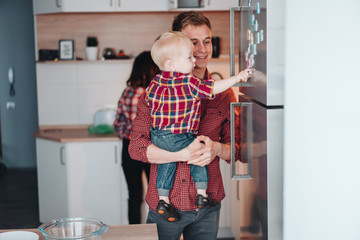 Dad and little son in the kitchen by the fridge