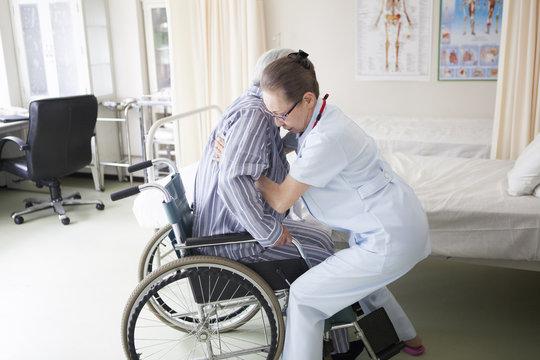 介護士が、リハビリ中の老人を車椅子に座らせている。