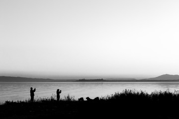 Silhouettes of a couple on a lake shore taking photos of sunset