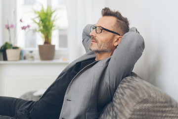 Mature man in grey jacket relaxing on sofa