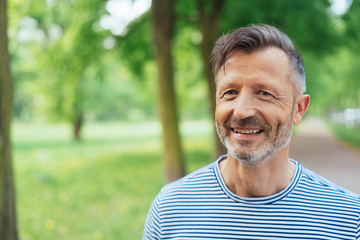 Happy mature man standing in park