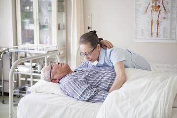 高齢者の患者をベッドから起こす看護師。