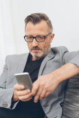 Mature man sitting on sofa with mobile phone
