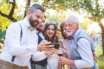 Bride, groom and guests with smartphones taking selfie outside at wedding reception.