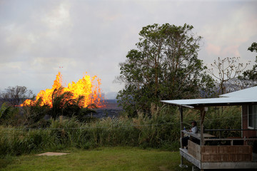 Homeowner Victor Hoapili sits on his porch watching the lava erupt from a fissure in the Leilani Estates near Pahoa, Hawaii