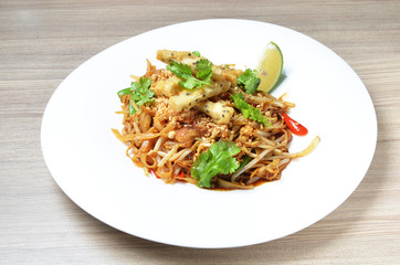 Thai style stir fried rice noodle on white plate.