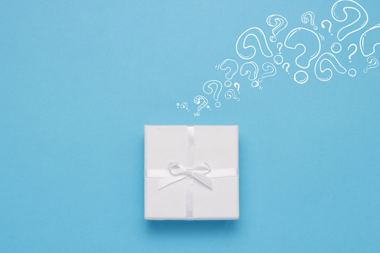 White gift box and Icon Question mark on a blue background. Minimalistic style. Concept surprise and suspense. Flat lay, top view