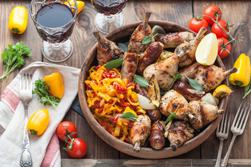 Roasted chicken with sausages and lemon. Tomatoes and wine