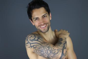 bel homme tatoué posant devant un fond gris