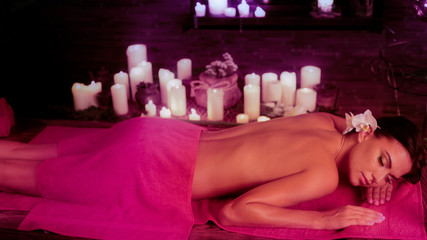 Massage of woman in spa salon. Girl on candles background in therapy room. Luxary interior in oriental therapy salon. Female have relax after sport. Violet toning image effect.