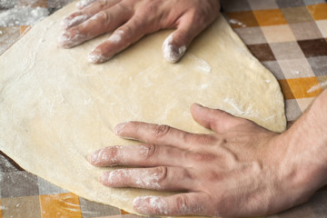 Cooking and home concept - close up of male hands kneading dough on a background in cell