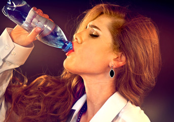 Sensitive teeth woman drinking cold water from bottle. Sudden toothache of thirsty girl in business suit drink. Lady with closed eyes guzzles on black background. Vulgarity and eroticism.