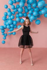Teenage girl in black dress dancing alone on her birthday party. Pink background with blue balloons