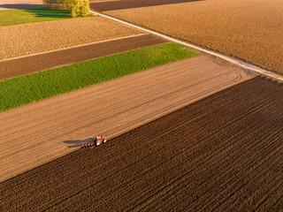 Aerial shot of a farmer plowing stubble field Wall mural