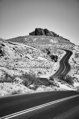Black and white picture of a scenic desert road, travel concept.