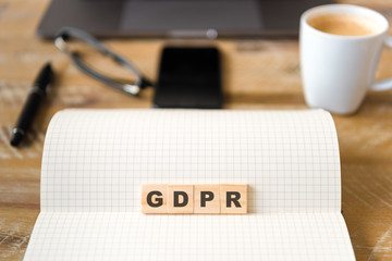 Closeup on notebook over wood table background, focus on wooden blocks with letters making GDPR General Data Protection Regulation text