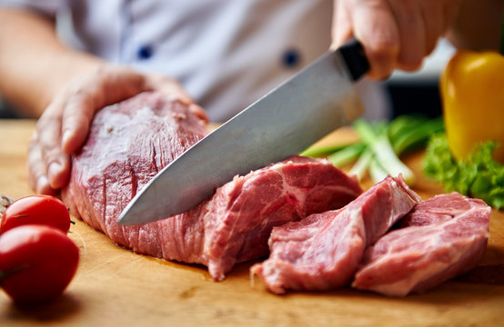 Portrait of chef hands cutting raw meat on wooden desk.