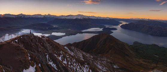 Woman hiker standing on a ledge of a mountain, enjoying the beautiful sunrise