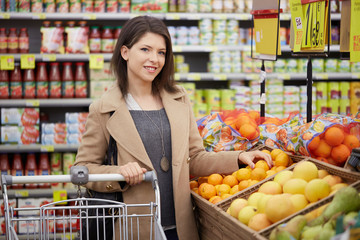 pretty woman buy fruits and vegetables at supermarket