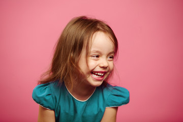 Portrait of beautiful little girl laughing happily on pink isolated background.