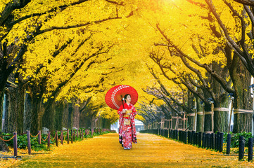 Aluminium Prints Orange Beautiful girl wearing japanese traditional kimono at row of yellow ginkgo tree in autumn. Autumn park in Tokyo, Japan.