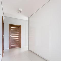 White hallway with wooden door