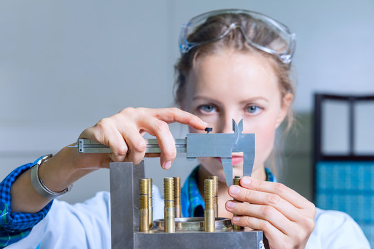 Woman engineer measures the size of the device in the modern lab