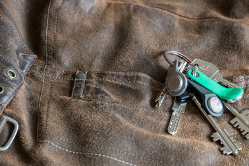 A bunch of keys on an old denim worn brown jacket. Worn texture of jeans. A pocket with a rivet. Pattern, design.