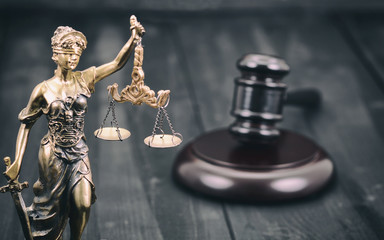 Scales of Justice, Judge Gavel, Justitia, Lady Justice on a black wooden background.