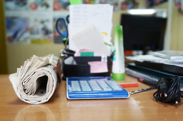 Rolled newspapers and pile of documents on desk. Business papers with latest news and paperwork. Business activity, concept for work at the office
