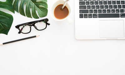 close up blank ecology white paper background with tropical leaves and coffee cup,glasses,pencil , copy space for idea your text,ads,content on image