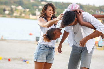 Young mixed race family hangout outdoors and making fun on beautiful summer day.
