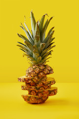 close up view of cut pineapple exotic fruit on yellow background