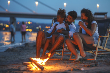 Young mixed race family sitting and relaxing at the beach on beautiful evening.They sitting by the camp fire.