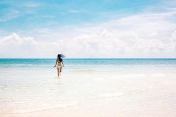 Young slim woman running to the sea