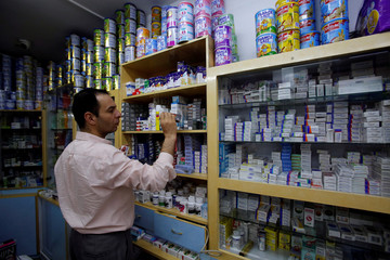 Palestinian pharmacist arranges medicines in a pharmacy in Hebron, in the occupied West Bank