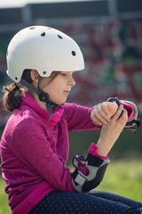 Close-up of skateboarder girl checking message on smartwatch.
