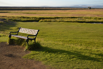 Icelandic landscape on a green field and bench