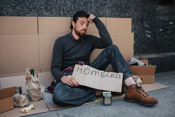 A picture of man sitting on the ground and holding homeless carboard in his hands. He is sad and tired. Guy is holding head with left hand and looking down. There are lots of stuff surround him.