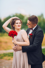 Portrait of a happy couple laughing at camera. Bridesmaid and groomsmen outdoor portrait. Funny wedding moment.