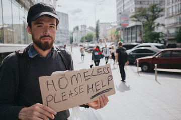 Homeless man is standin on the street and showing the sign which says homeless please help. Guy is waiting for somebodie's help. He looks serious and tired.