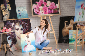 Art school student girl with her painting on exhibition show in a studio